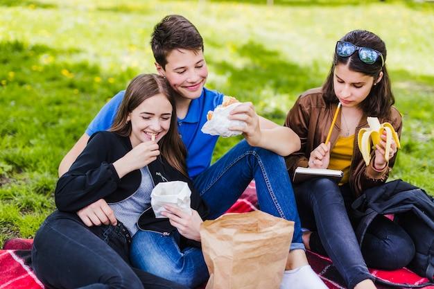 Les élèves mangent sur l'herbe