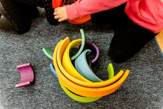 Élèves manipulant du matériel de montessori dans une école sur un tapis pendant un cours.