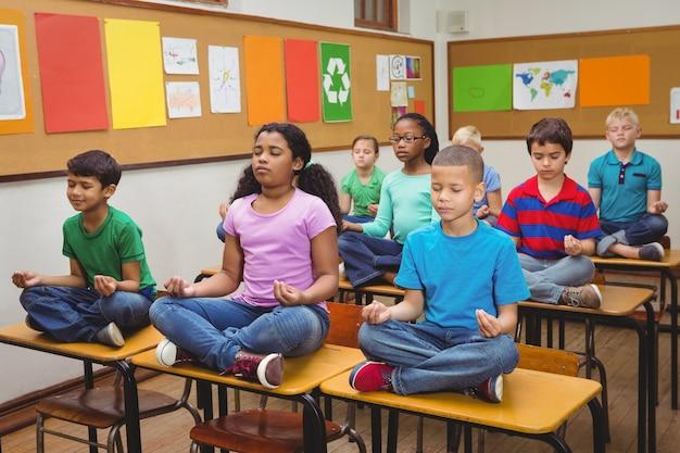 Les élèves méditent sur les bureaux de classe