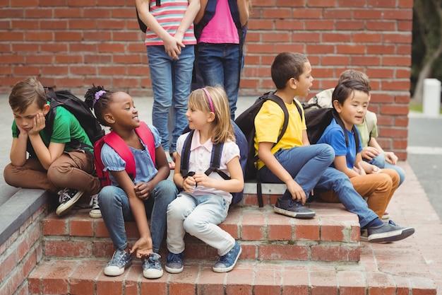 Élèves mignons assis sur les marches à l'extérieur