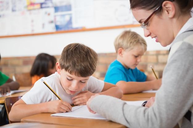 Élèves mignons écrit au bureau dans la salle de classe