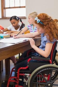 Élèves mignons écrivant au bureau dans une salle de classe à l'école primaire