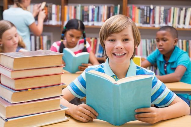 Élèves mignons lisant dans la bibliothèque