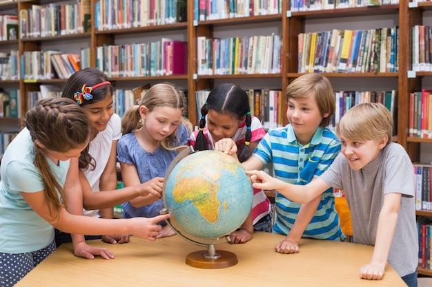 Élèves mignons regardant globe dans la bibliothèque