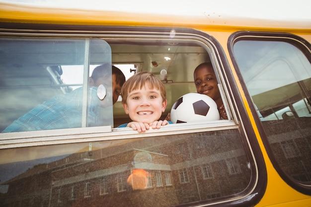 Élèves mignons, souriant à la caméra dans le bus scolaire