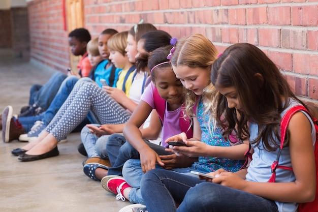Élèves mignons utilisant un téléphone portable