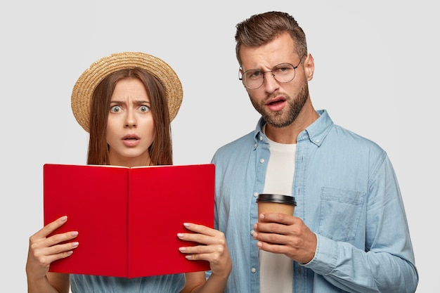 Des élèves perplexes et mécontents portent un livre ouvert, lisent des informations