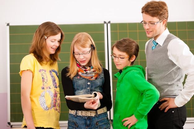 Élèves avec professeur sur tableau noir à l'école