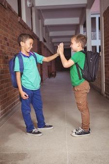 Les élèves se donnent un high five sur les terrains de l'école primaire