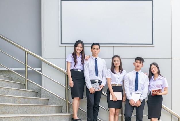 Les élèves se lèvent et sourient dans les escaliers avec un panneau blanc