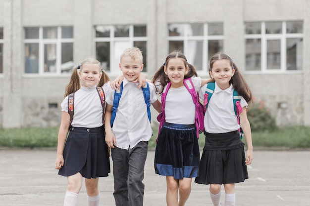 Élèves souriants, serrant près de l'école