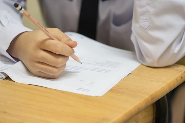 Élèves utilisant un crayon lisant des informations sur du papier blanc au lycée