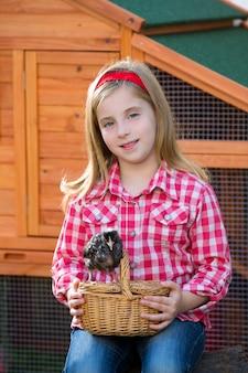 Éleveur poules enfant fille fermier éleveur avec poussins au poulailler