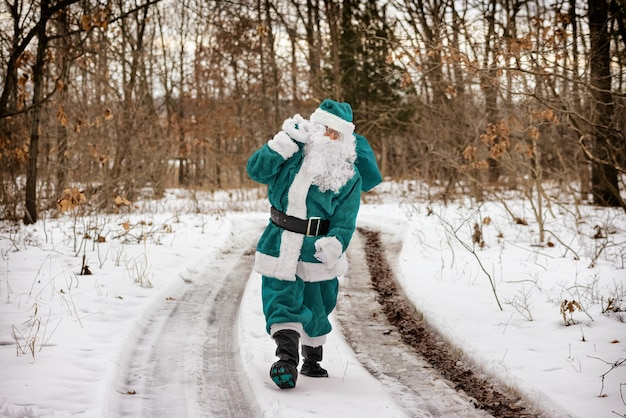 Elfe de noël en robe de costume vert apporte la marche à travers la forêt d'hiver transportant des cadeaux de noël du nouvel an et en détournant les yeux