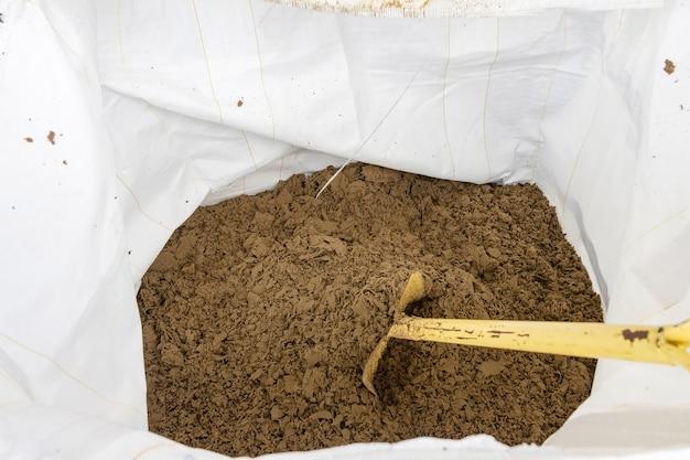 Élimination des boues noires du traitement des eaux usées dans un sac en plastique blanc