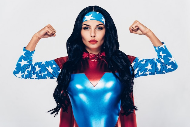 Elle a beaucoup de force. belle jeune femme en costume de super-héros regardant la caméra