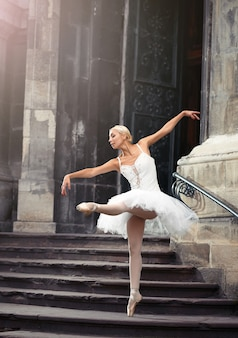Elle donne envie de danser. portrait flou d'une superbe interprète de ballet féminin à l'extérieur