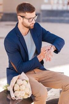 Elle est encore en retard. jeune homme inquiet en veste intelligente regardant sa montre alors qu'il était assis sur le banc avec un bouquet de roses posé près de lui
