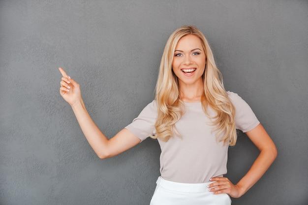 Elle ne donne jamais de mauvais conseils. cheerful young blonde woman pointing loin et
