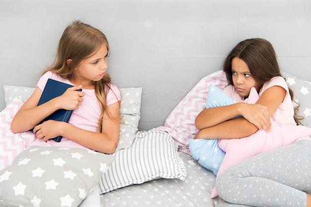 Elle ne veut pas partager son livre. concept de rivalité entre sœurs. problèmes de relations entre sœurs. partagez le livre avec un ami. les enfants dans la chambre veulent lire le conte de fées du soir. c'est mon livre. rivalité de filles.