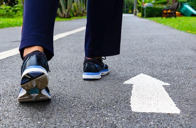 Elle porte des chaussures et s'avance sur la route