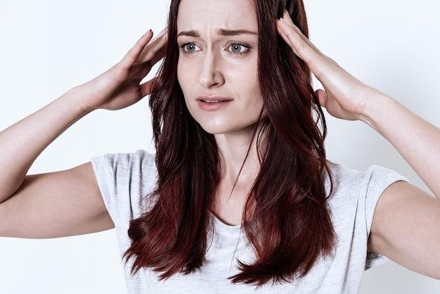 Elle porte ses mains à sa tête dans la salle blanche.