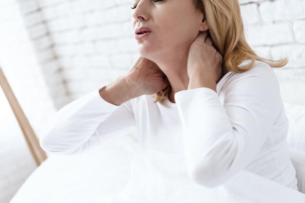 Elle porte ses mains à son cou sur un mur blanc.