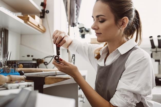 Elle sait ce qu'elle fait vue latérale d'une jeune joaillière préparant les outils pour