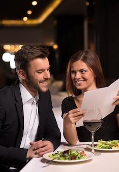 Elle sait ce qu'elle veut. belle jeune regardant le menu et souriant alors qu'il était assis au restaurant