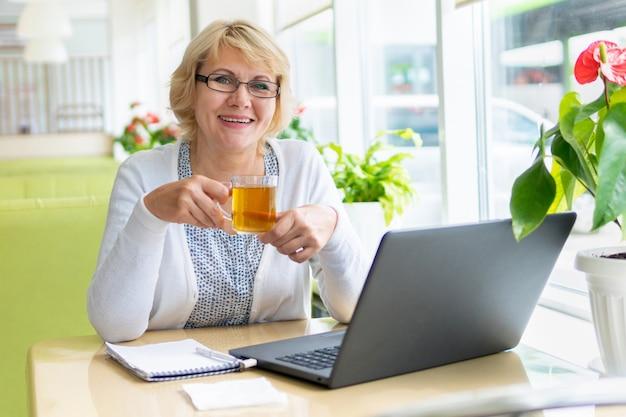 Elle travaille sur un ordinateur portable dans un café. une femme d'âge moyen boit du thé et regarde les informations. il est situé dans le bureau.