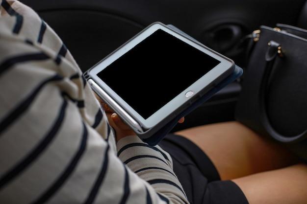 Elle utilise une tablette blanche dans les accessoires de voiture est de couleur noire