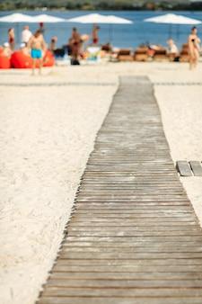 Éloignez-vous des planches de bois sur la plage de sable près du lac. chemin étroit pour les personnes se relaxant à l'extérieur. heure d'été et concept de nature.