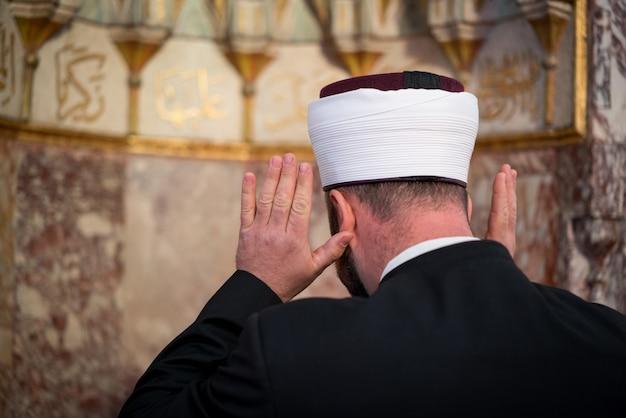 Emam dans la mosquée avec des vers de kuran sur le mur