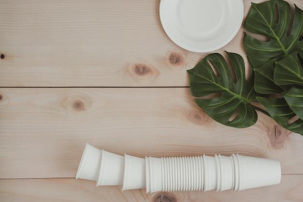 Emballage alimentaire en papier, gobelets en papier jetables écologiques, compostables et recyclables et assiette avec des branches de plantes sur fond en bois.