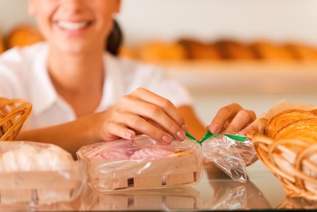 Emballage de biscuits à vendre. belle jeune femme en tablier emballant des biscuits et souriant en se tenant debout dans une boulangerie