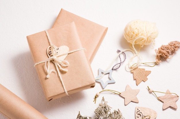 Emballage de boîte-cadeau écologique pour noël ou nouvel an, jouets de noël en bois, boîte enveloppée dans du papier kraft avec une branche d'épicéa et un coeur en bois sur fond blanc