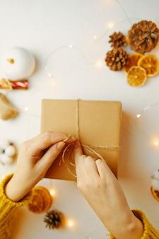 Emballage de boîte-cadeau de noël pour femmes, ruban à nouer dans des pommes de sapin, des tranches d'orange sèches et d'autres ...