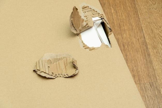 Emballage de boîte en carton endommagé et déchiré avec trou