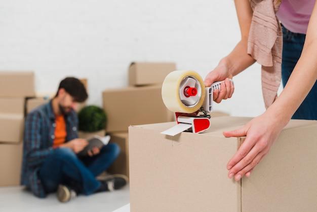 Emballage des boîtes avec du ruban de construction afin d'emménager dans de nouveaux logements