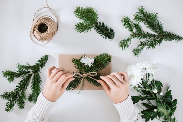Emballage cadeau avec du papier naturel, du sapin et des fleurs blanches.