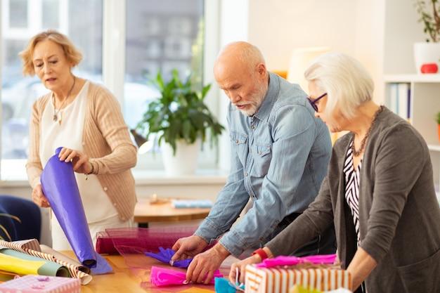 Emballage cadeau. des gens joyeux et agréables s'amusant tout en profitant de leur activité créative