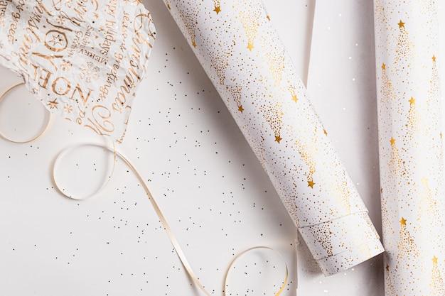 Emballage cadeau. papier d'emballage festif pour noël,. couleurs festives blanches, dorées, argentées. saison des fêtes. emballage de boîte de cadeau à la main.
