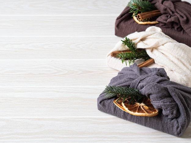 Emballage cadeau réutilisable en tissu écologique avec brunch au sapin, bâton de cannelle et tranche d'orange sèche. alternative d'emballage-cadeau durable réutilisable de noël. concept zéro déchet.
