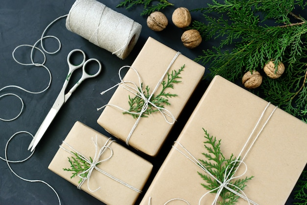 Emballage de cadeaux de noël écologiques avec du papier kraft, des ficelles et des branches de sapin naturel sur fond sombre