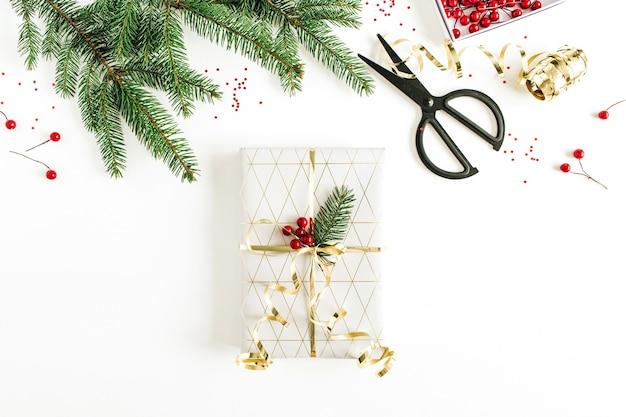 Emballage de cadeaux de noël, nouvel an. composition de vacances avec des décorations, des baies rouges et des branches de sapin sur une surface blanche. mise à plat, vue de dessus