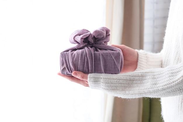 Emballage de cadeaux en tissu pour noël dans un style furoshiki. concept écologique. diy