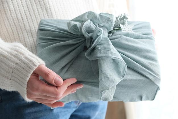 Emballage de cadeaux en tissu pour noël dans un style furoshiki. concept écologique.