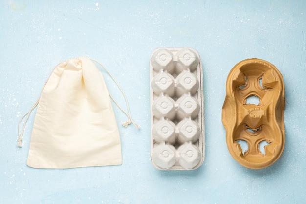 Emballage écologique pour œufs, café et sac en coton sur fond de ciment bleu. concept zéro déchet. achats alimentaires sans emballage. vue de dessus.place pour le texte