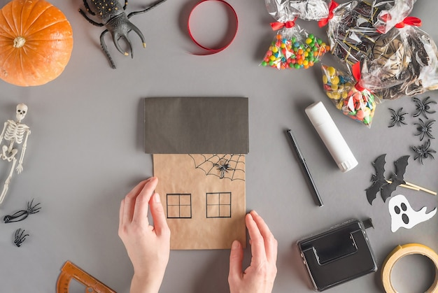 Emballage étape par étape d'un cadeau pour halloween, collez l'araignée en plastique sur la toile