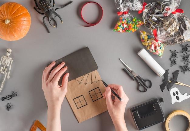 Emballage étape par étape d'un cadeau pour halloween, dessinez les lignes transversales de la toile avec un feutre
